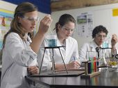 stock photo of flask  - Teenage students caring out experiments in chemistry class - JPG