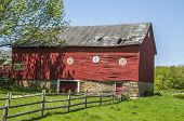 pic of red barn  - A large red barn in disrepair with a stone foundation