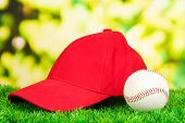 Red peaked cap on grass on natural background