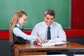 Little girl asking question to male teacher at desk in classroom