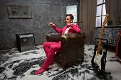Young man in pink suit sits in scuffed old armchair in room powdered with snow