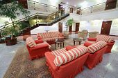 Atrium with red soft armchairs, couches and stairs in stylish hotel.