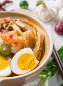 Prawn noodles or prawn mee. Famous Singapore food spicy fresh cooked har mee in clay pot with hot st