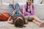 Two girls with mp3 player and cell phone