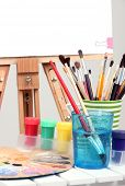 Wooden easel with clean paper and art supplies in room