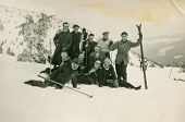 ZAKOPANE, POLAND - CIRCA 1950 - vintage photo of group of friends posing with ski in snowy mountains