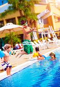 Happy family having fun in the pool, son jumping into the water, relaxed in aquapark, beach resort, summer vacation, travel and tourism concept