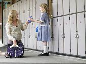 Happy mother packing daughter's school bag near school lockers