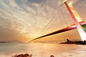 stock photo of tsing ma bridge  - Sunset cityscape with famous Tsing Ma bridge over water in Hong Kong - JPG