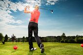 foto of swings  - Young female golf player on course doing golf swing - JPG