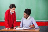 Young African American female teacher and schoolgirl reading together at desk in classroom