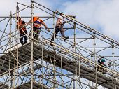 stock photo of workplace safety  - construction worker on a scaffold - JPG