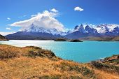 The strong wind drives turquoise waves on the lake, grandiose rocks Los Kuernos are covered with sno