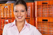 Portrait of young beautiful woman standing against stack of baskets in laundry