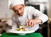A Chef Arranging Tossed Salad In A White Bowl