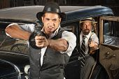 foto of tommy-gun  - Angry 1920s vintage gangsters at car with weapons - JPG