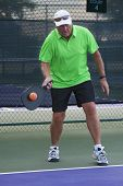 stock photo of pickleball  - Senior man returning in a serve during pickleball match - JPG