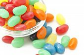 picture of jelly beans  - Colorful jelly beans spilling out a small bowl on a white background - JPG
