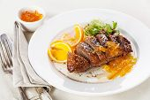 stock photo of duck breast  - Roasted Duck Breast with orange sauce on white - JPG