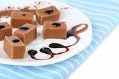 image of toffee  - Many toffee on plate on napkin isolated on white - JPG