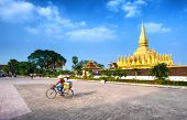 VIENTIANE, LAOS - 11 DEC,2013: Unidentified local woman on the bicycle on the square near golden pag