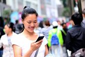 young asian woman use her cell phone on shopping street