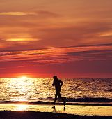 Woman Running At Beautiful Sunset In The Beach.