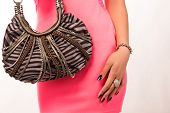 Closeup of woman in pink mini dress. Wearing a fashion leather bag. Isolated on the white studio bac