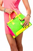 Closeup of woman with neon green and pink bag. Wearing mini lace dress. Isolated on the white studio background