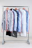 Office male clothes in cases for storing on hangers, on gray background