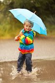 Boy splashing in puddle smiling holding a blue umbrella
