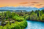 stock photo of bend over  - Beautiful sunset over the bend of the river Clutha with Southern Alps peaks on the horizon - JPG
