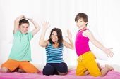 foto of pillow-fight  - mother and her two sons having a pillow fight in bedroom - JPG