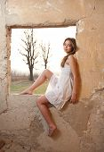 Sensual lady in white dress looking to the window and red sun behind her. Beautiful girl