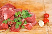 fresh raw beef meat slices over a wooden board with dill , green  and red hot peppers isolated over