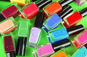 Group of bright nail polishes, on green background