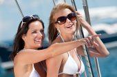 Twee aantrekkelijke lachende vrouw op zeilboot