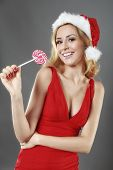happy smile girl wearing a santa suit holding a candy for christmas on grey background