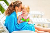 Mother And Baby Girl Wrapped In Towel Sitting On Sunbed