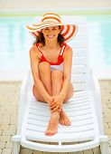 Portrait Of Smiling Young Woman In Hat Sitting On Sunbed