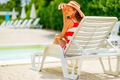 Relaxed Young Woman In Hat Sitting On Sunbed. Rear View