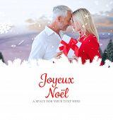 loving couple with gift against joyeux noel