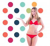 Fit blonde in red bikini showing scales against colorful polka dot pattern