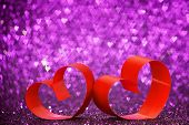 Red ribbon hearts on purple glitters, Valentines day concept