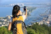 young woman hiker use smart phone taking self photo at mountain peak