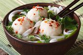 Asian Soup With Fish Balls, Fresh Herbs And Rice Noodles Close-up