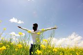 stock photo of open arms  - cheering woman open arms at cole flower field - JPG