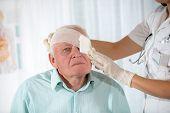 Nurse bandaging older man eyes