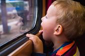 stock photo of passenger train  - Small boy traveling by train his face reflected in the glass
