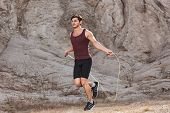foto of jump rope  - sporty man jumping rope outdoors in the morning - JPG